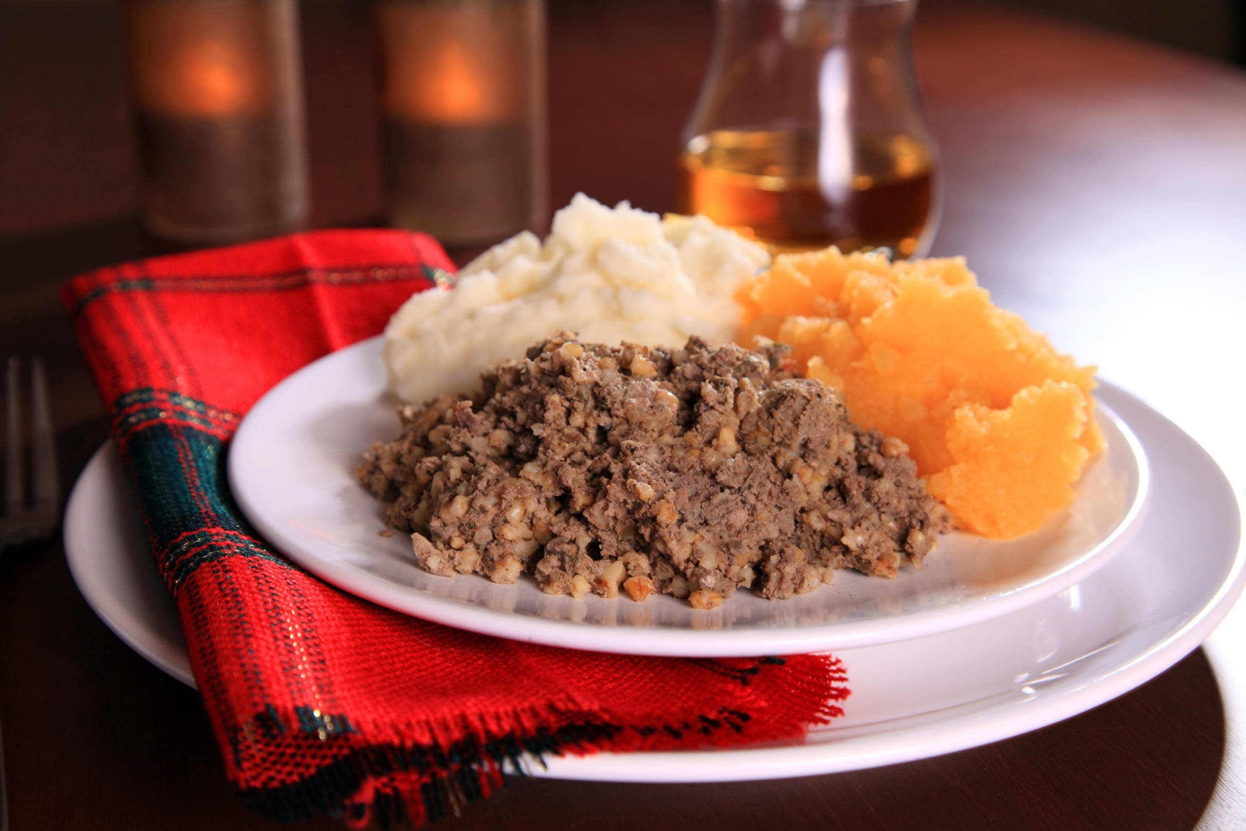 A Burns Night supper of haggis and tatties on a plate with a tartan napkin.