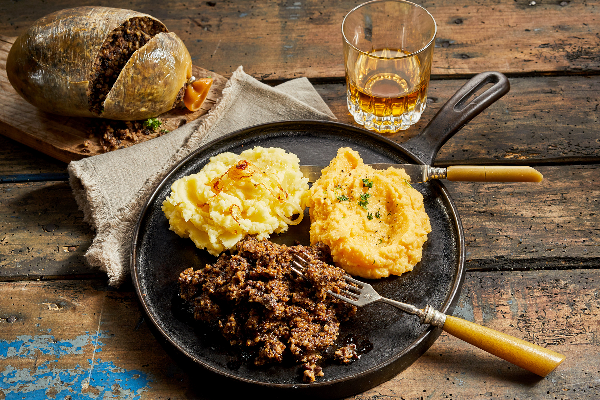Rustic meal of haggis, neeps and tatties served with a tumbler of whisky to celebrate Robert Burns Supper in a high angle view