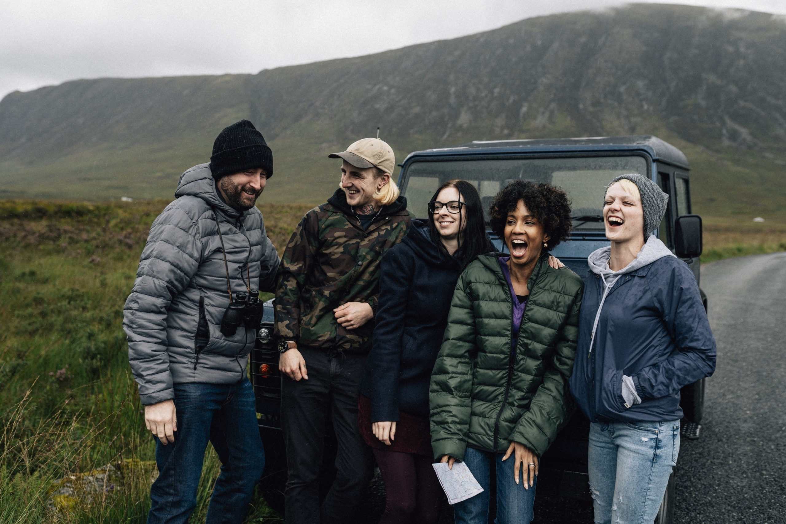 A group of friends taking a break from driving in Scotland, laughing and using Scottish slang