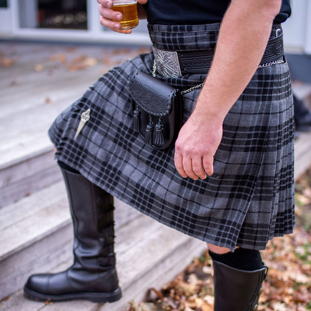 A man wearing a kilt, sporran, and boots  while holding a beer.