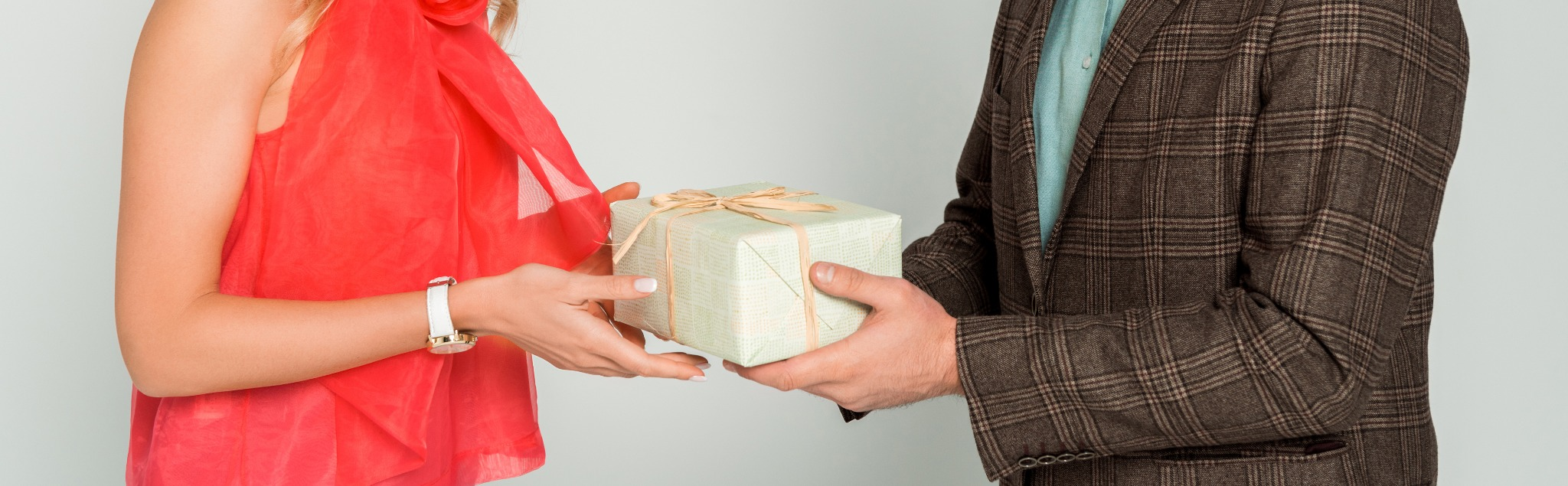 A man and woman exchanging a Scottish-themed gift