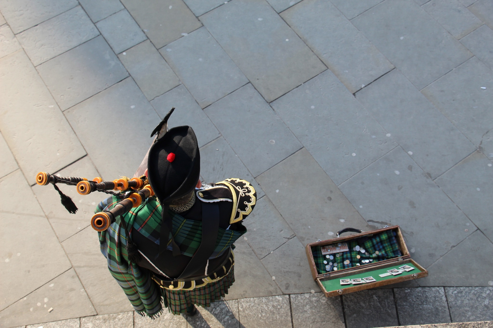 An aerial view of a bagpipe player busking and wearing a Glengarry hat
