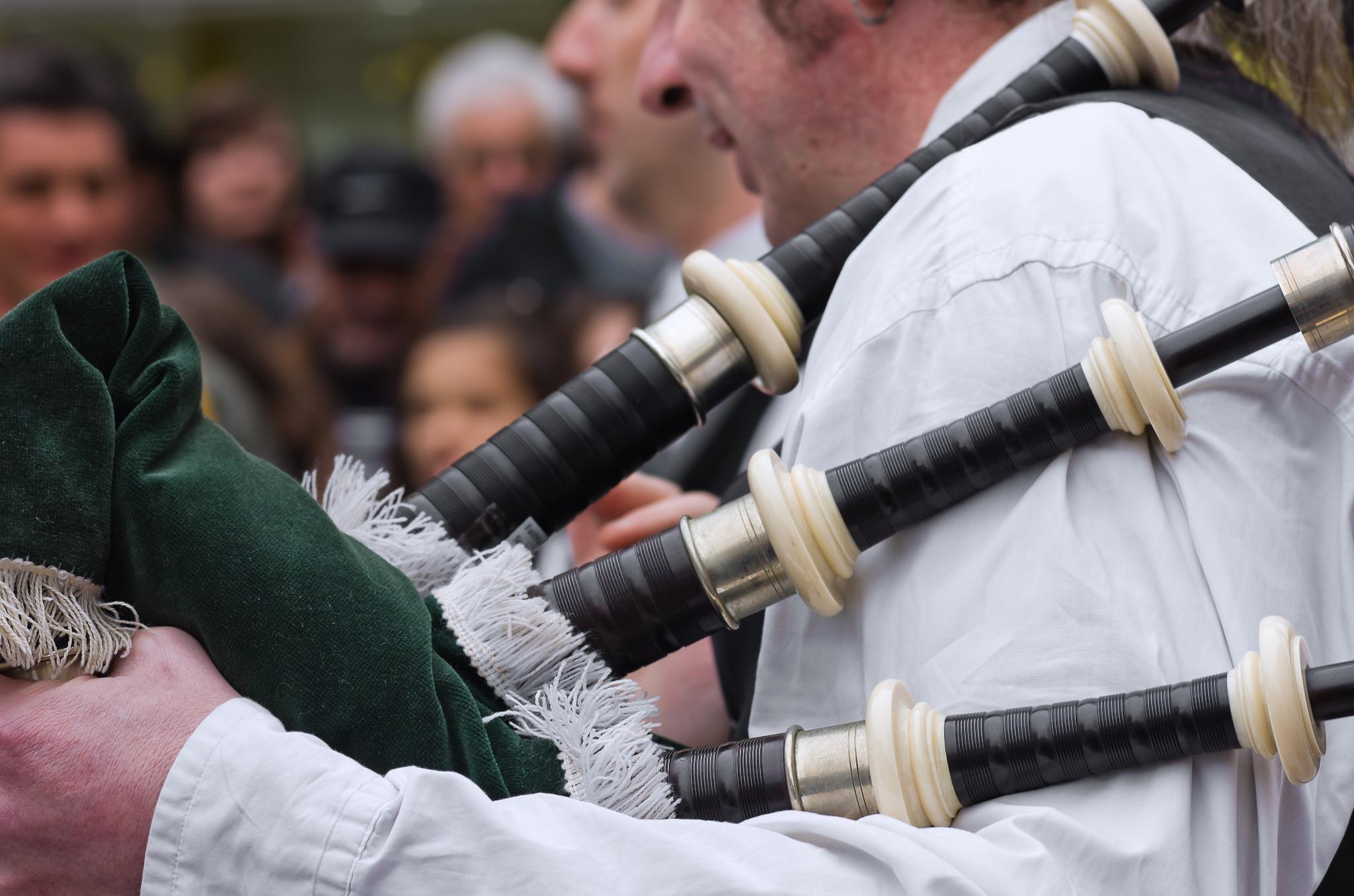 A close up shot of a man holding a dark green bagpipe at a parade.