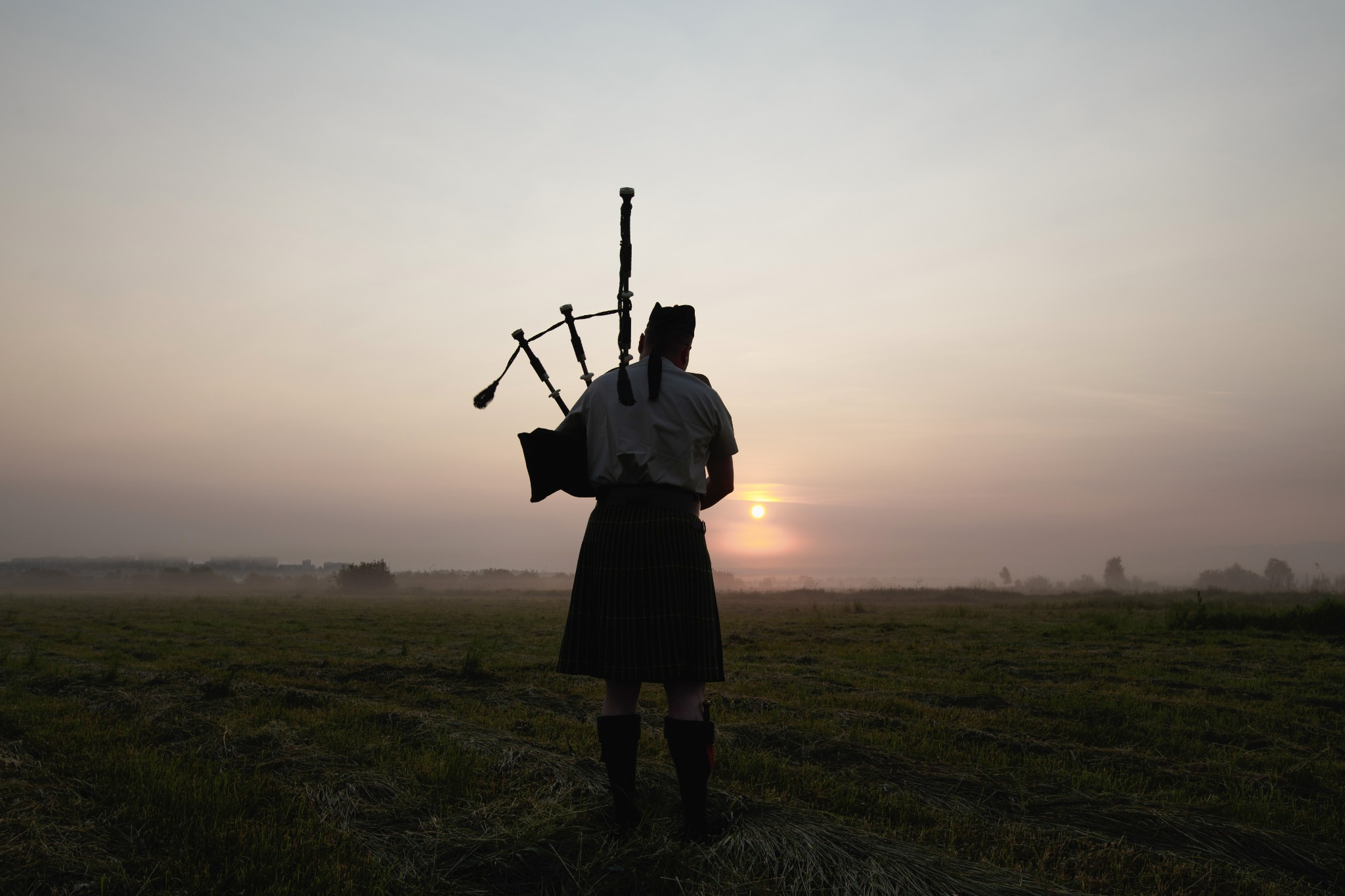 A man playing a bagpipe during a Scottish sunset.
