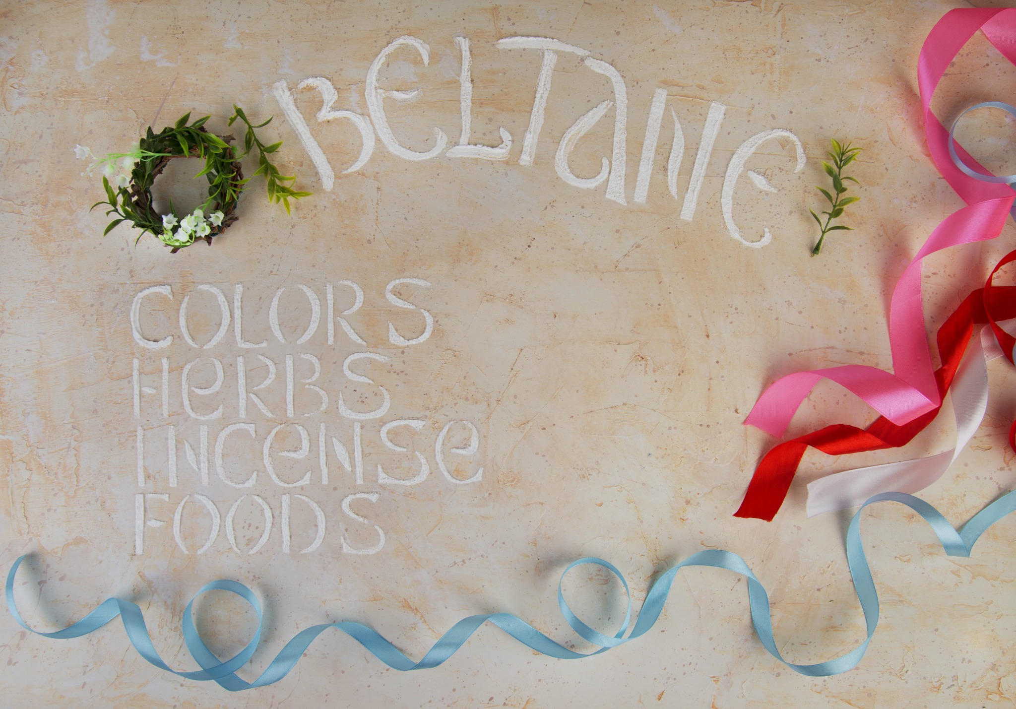 Beltane written out with herbs, colors, and ribbons.