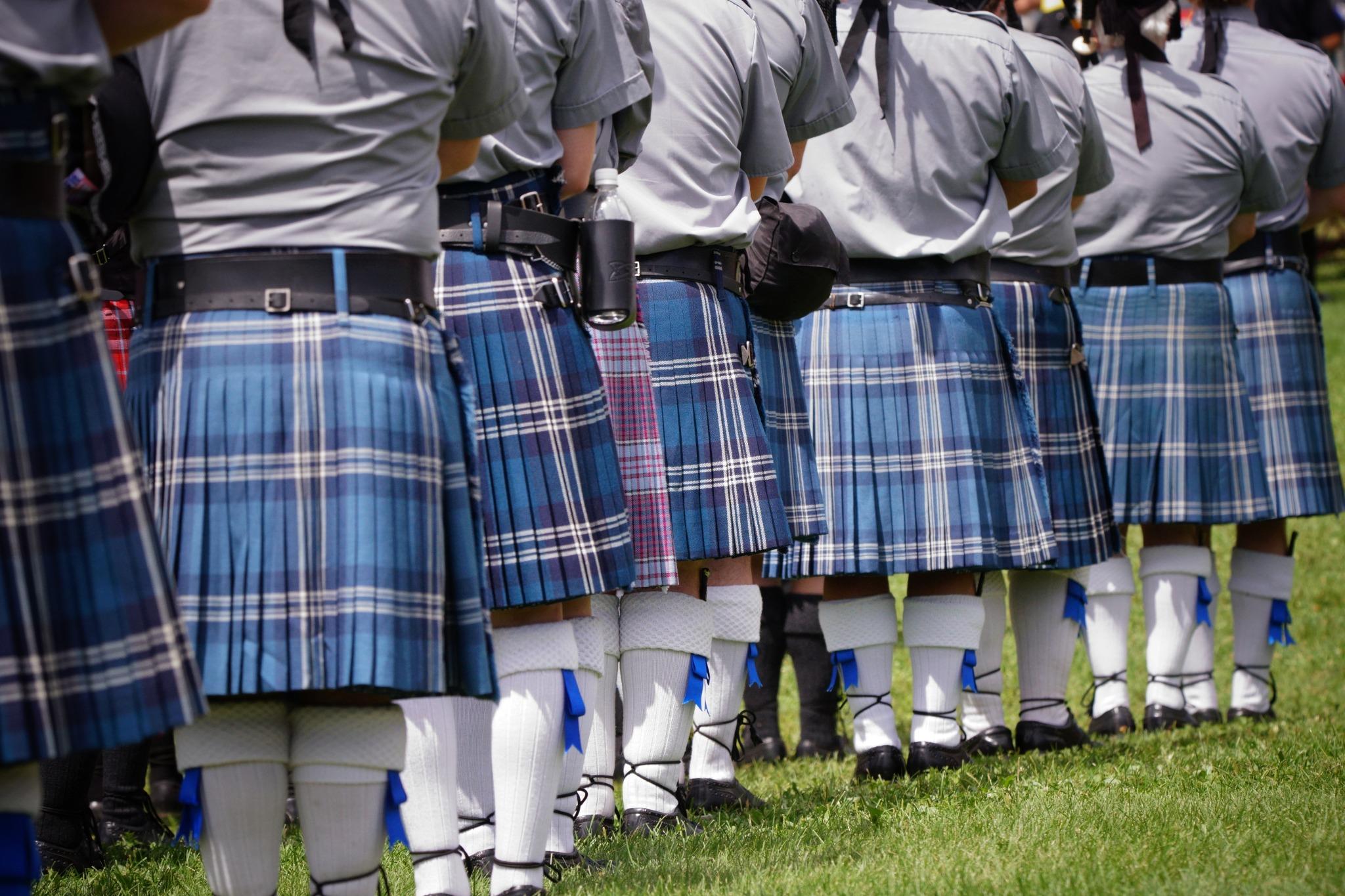 Men standing in a line wearing matching clan tartan kilts