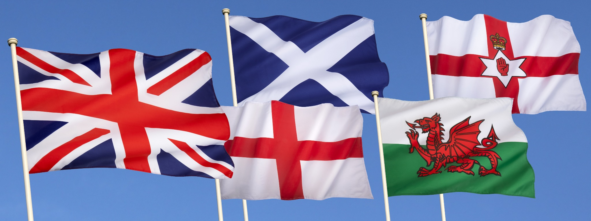 The flags of Great Britaina nd Ireland including the Welsh Drago, St. Andrew's Cross, Ulster Flag, the Union Jack and the flag of Northern Ireland.