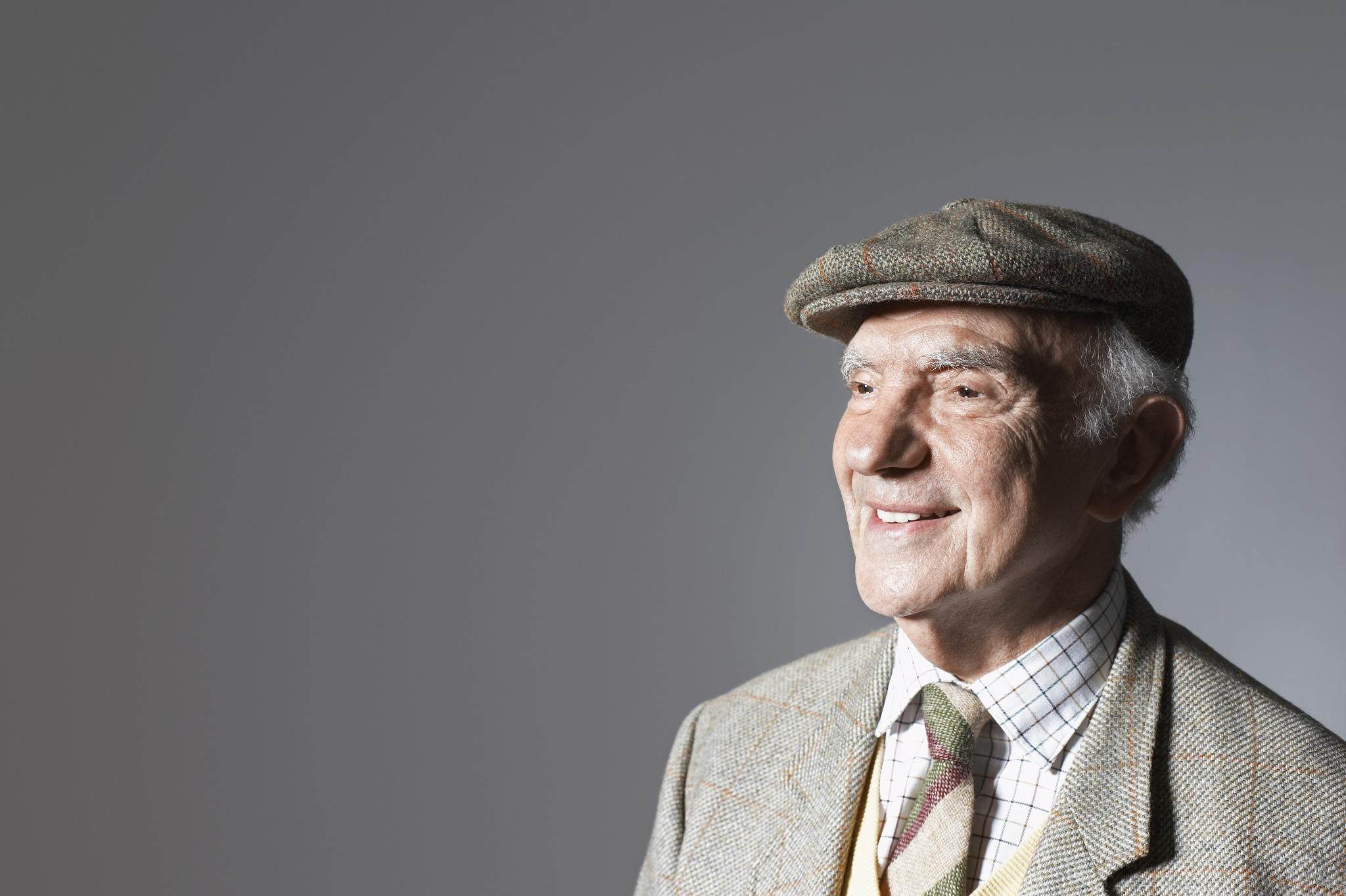 An older gentleman smiling and wearing a flat cap.
