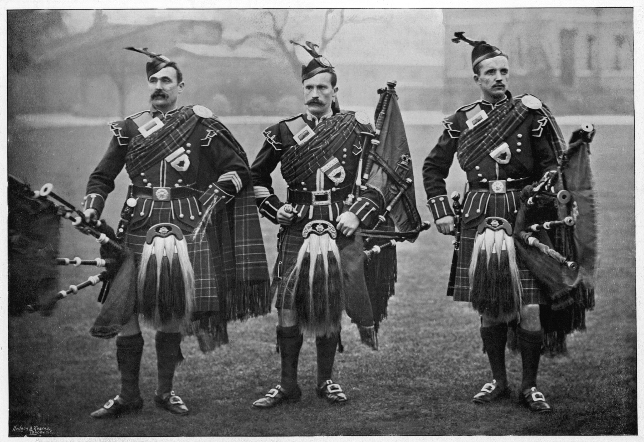 Three men in a black and white historical photo wearing sporrans and bagpipes.