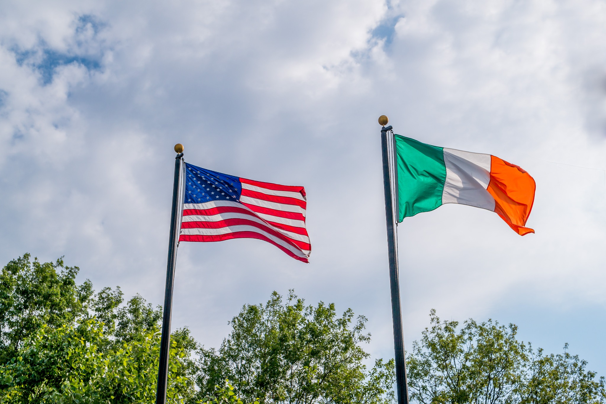 The American flag and Irish flag flying next to each other to celebrate Irish-American heritage.
