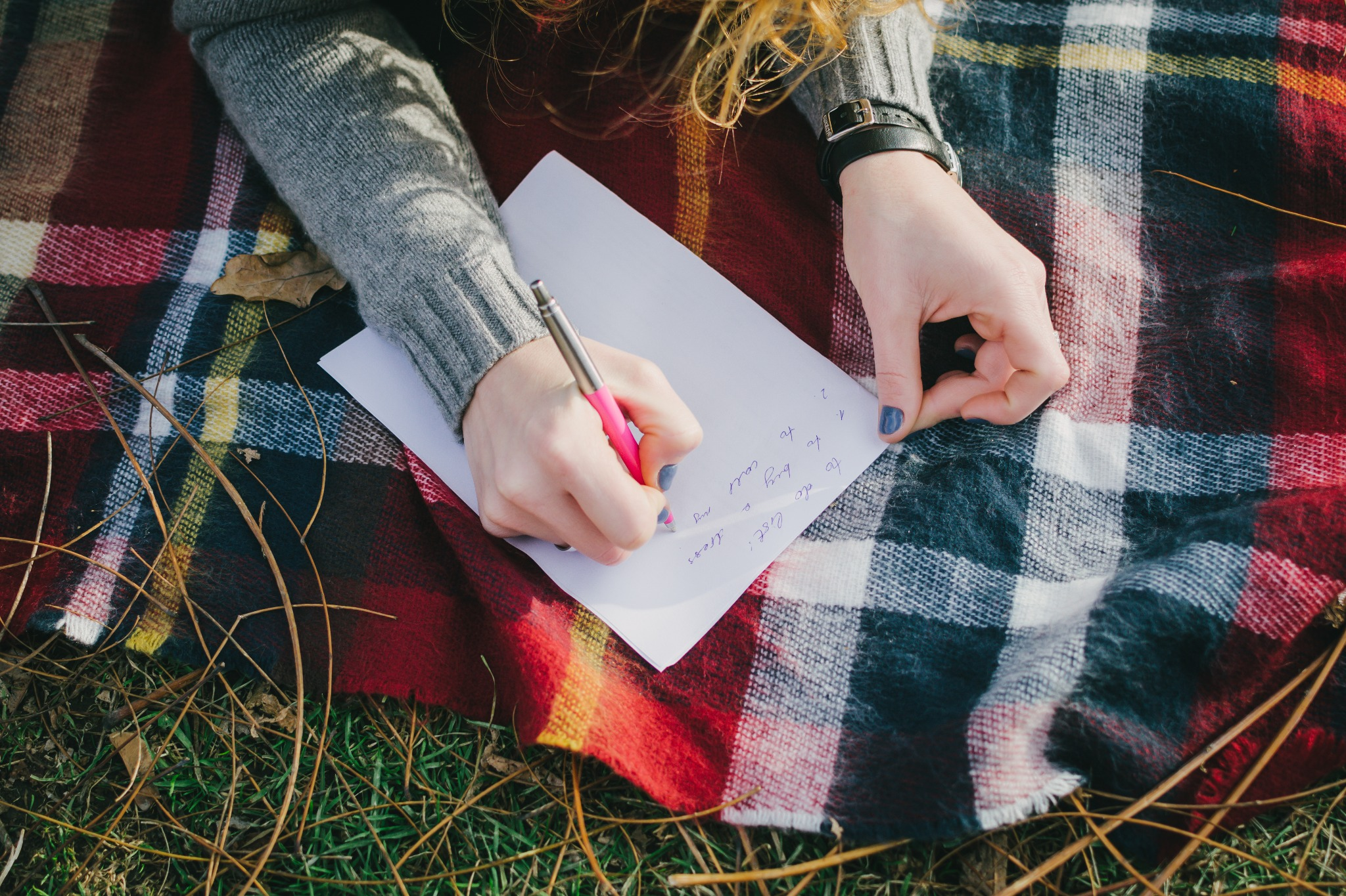 A person journaling outdoors while laying on a tartan blanket to reflect during Beltane.