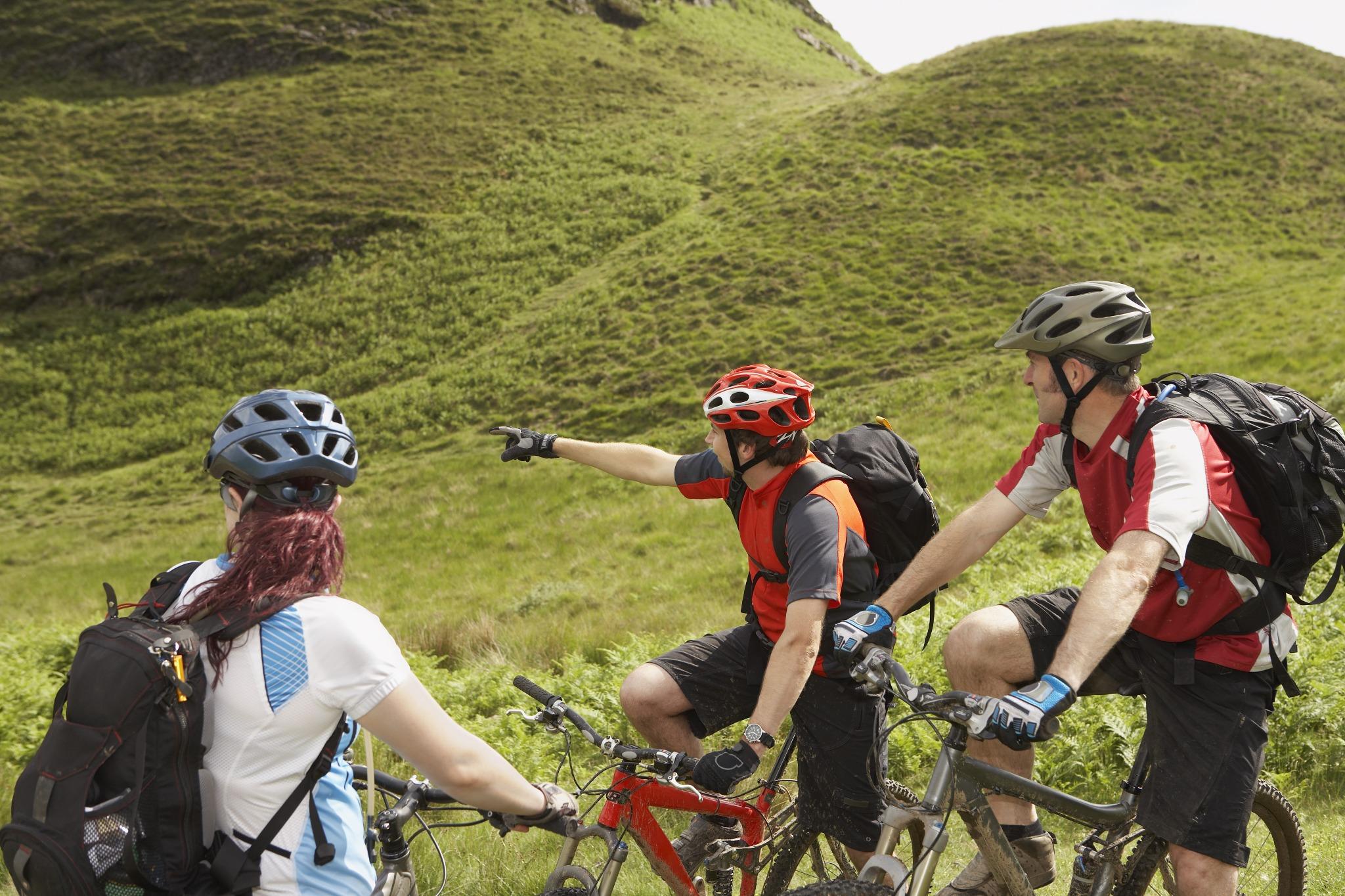 Three people mountain biking in Scotland.