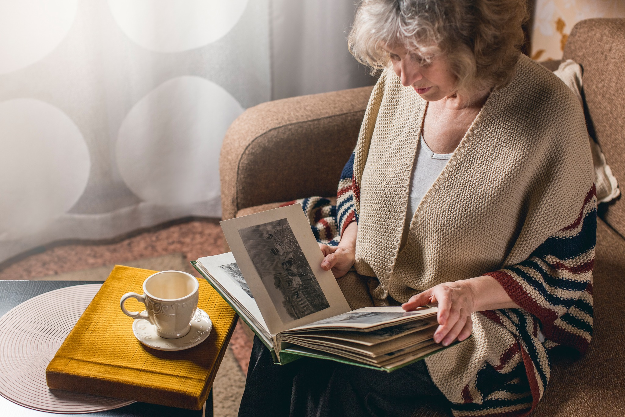 A elderly woman experiencing Hiraeth (the Welsh word for nostalgia) while looking at a photo album and having tea.