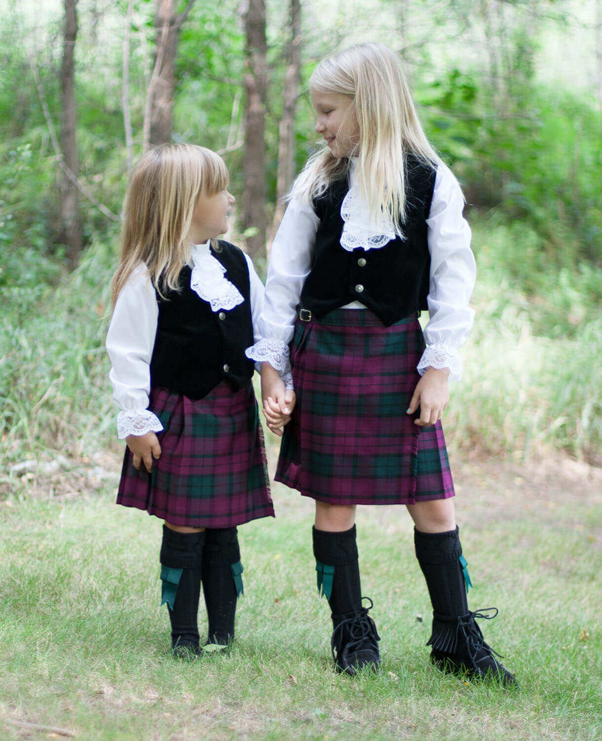 Two little girls wearing kilts they received as Christmas gifts