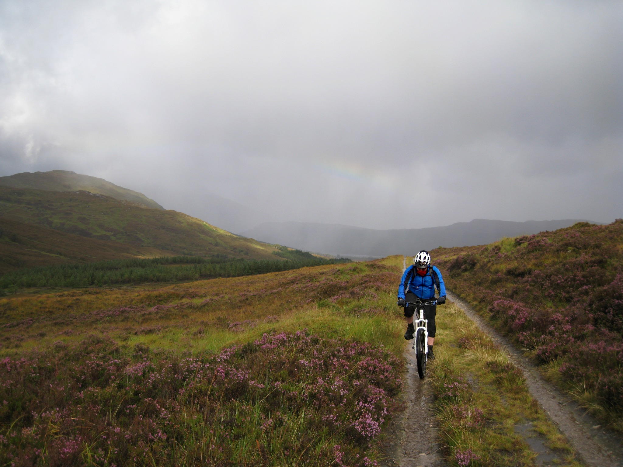A cyclist riding in the rain in the Scottish Highlands