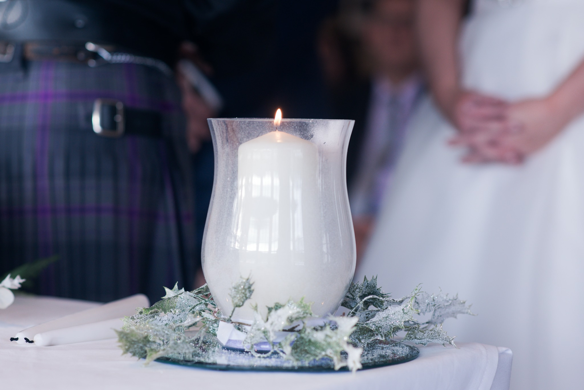 A Scotish wedding with a white candle.