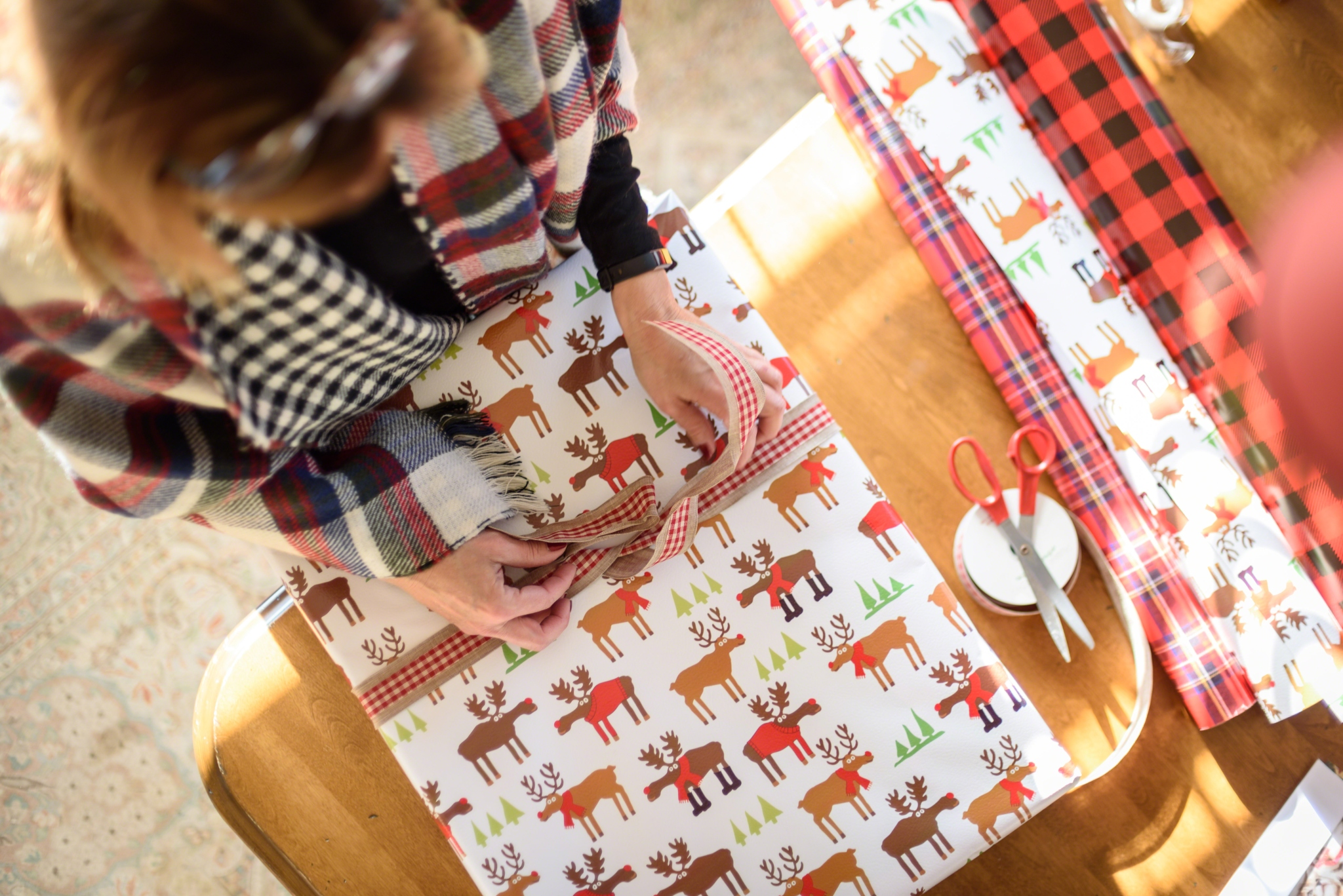 A woman wrapping Christmas gifts for her family that she purchased at the Celtic Croft online
