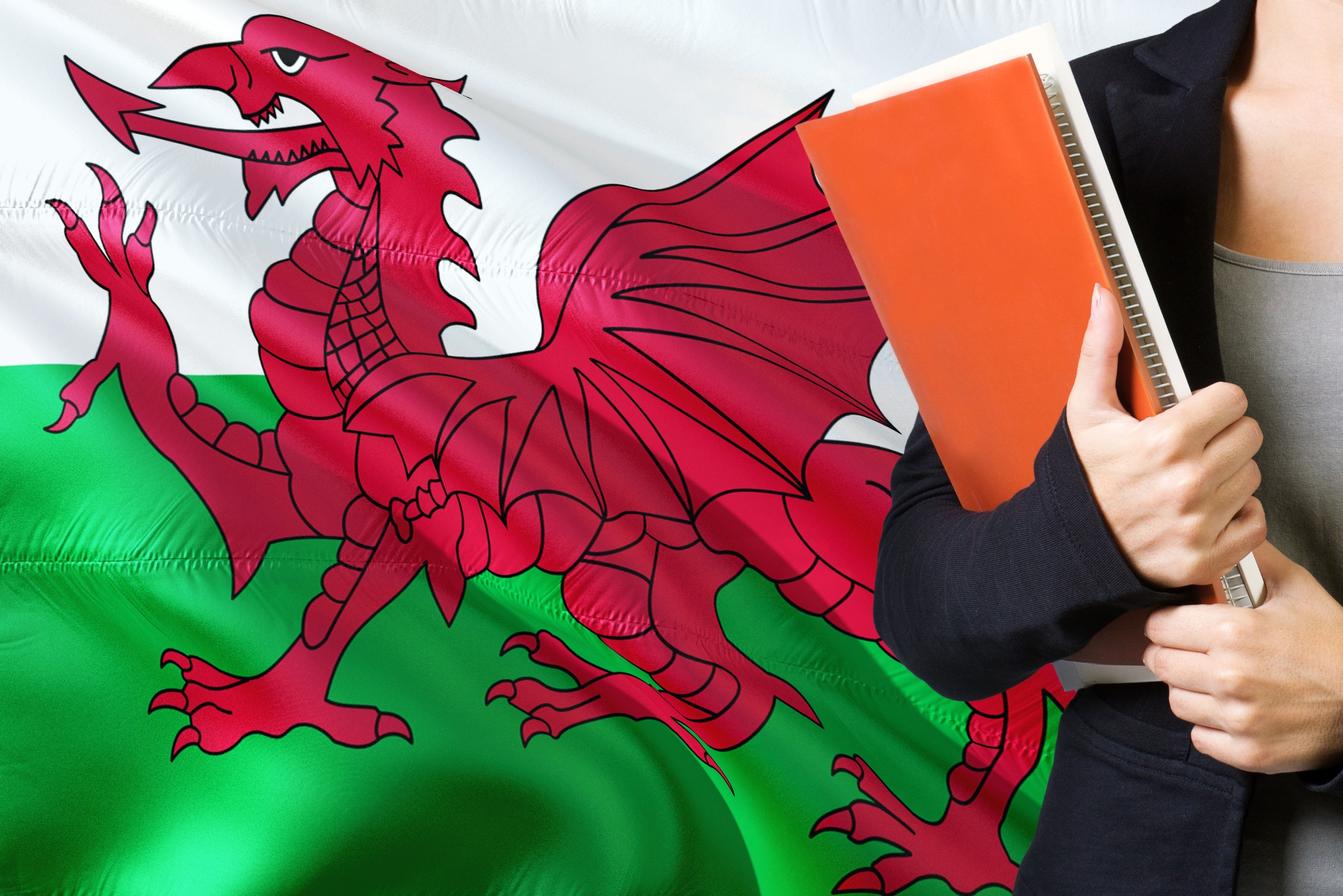 A woman holding a large notebook in front of a large Welsh flag