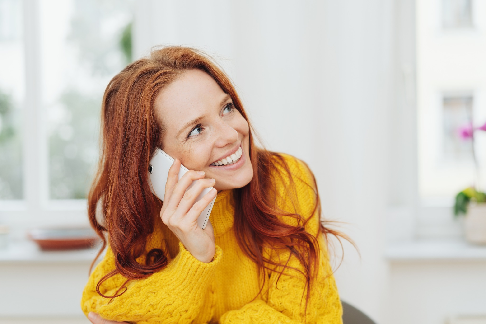 """A red-headed woman talking on the phone and smiling, asking how someone is, or the Welsh phrase """"Su'mae"""""""